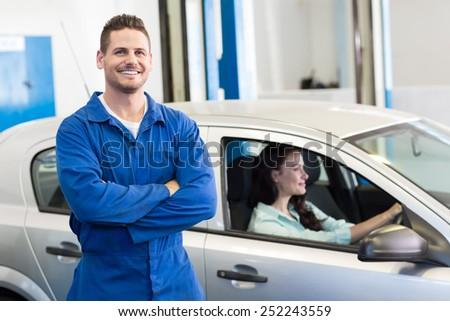Mechanic smiling at the camera at the repair garage - stock photo