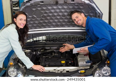 Mechanic smiling at the camera with customer at the repair garage - stock photo