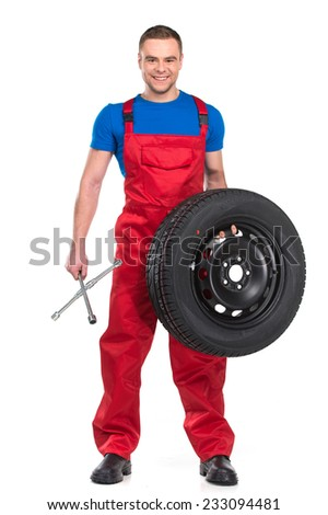 mechanic standing and holding wrench and tire. smiling man looking into camera on white background - stock photo