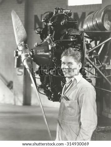 Mechanic standing next to propeller - stock photo