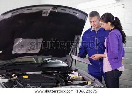 Mechanic standing with a clipboard next to a client in a garage