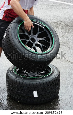 Mechanic takes a wheel mounted with wet tyre while rain is falling during a race on circuit in Spa, Belgium - stock photo