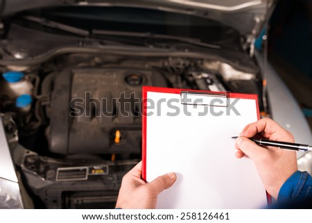 Mechanic taking notes on broken car - stock photo
