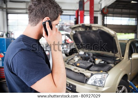 Mechanic talking on cell phone in garage - stock photo