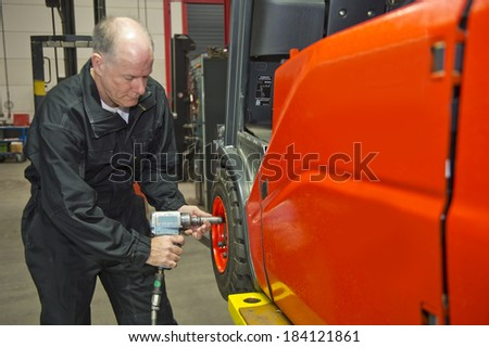 Mechanic tightens wheel nuts on a fork lift with a pneumatic wrench
