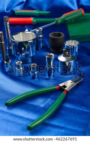Mechanic tools set on blue silk background. The different sizes wrench socket and hand tools with green handles