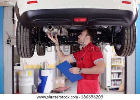 mechanic under the car made inspection - stock photo