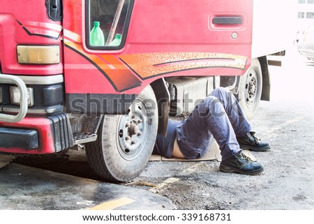 Mechanic under truck repairing dirty greasy oily engine with problem. - stock photo
