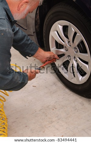 Mechanic using a air pressure gage/inflation tool while rotating the tires on a vehicle - stock photo