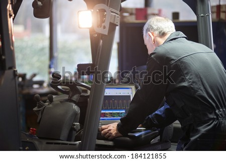 Mechanic using a laptop to interface with a forklift's electronics and engine - stock photo