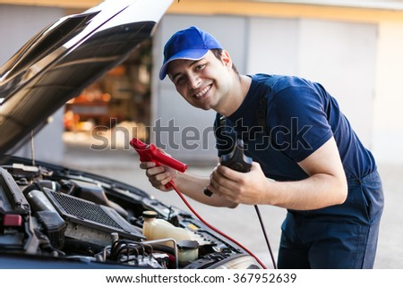 Mechanic using booster cables to startup a car engine - stock photo