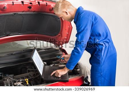 Mechanic Using Laptop While Repairing Car In Garage - stock photo