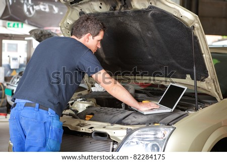 Mechanic using laptop while repairing car in garage - stock photo