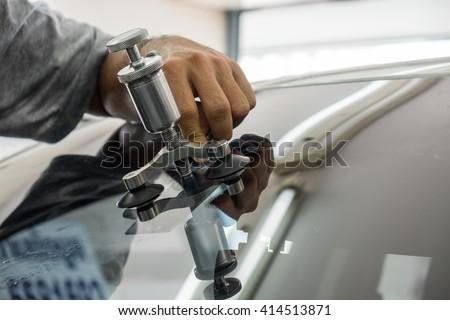 Mechanic using repairing equipment to fix damaged windshield, windshield repairing, - stock photo
