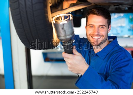 Mechanic using torch to look under car at the repair garage - stock photo