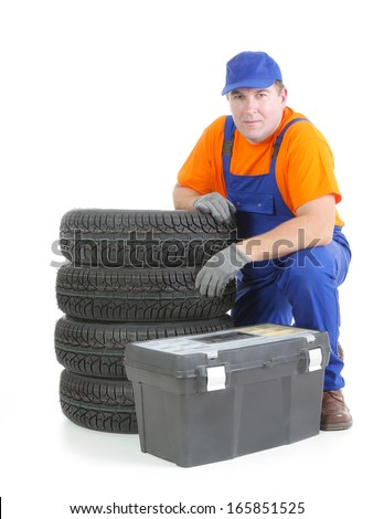 Mechanic wearing blue coveralls and orange t-shirt posing by pile of four new car tires and toolbox shot on white - stock photo