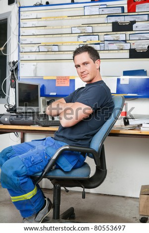 Mechanic with arms crossed sitting on a chair and smiling - stock photo