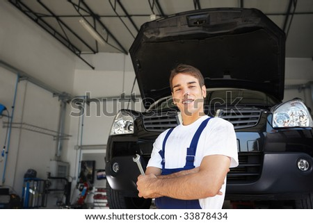 Mechanic with arms folded  in auto repair shop. - stock photo