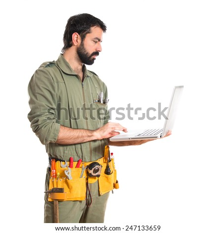mechanic with laptop over white background  - stock photo