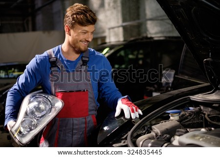 Mechanic with new car headlight in a workshop