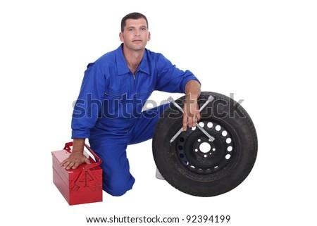 Mechanic with wheel - stock photo
