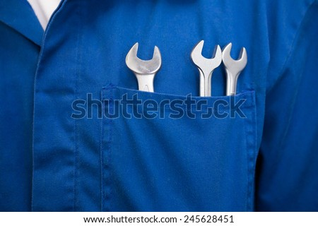 Mechanic with wrenches in pocket at the repair garage - stock photo