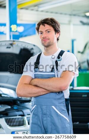 Mechanic working in car workshop - stock photo