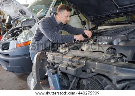 mechanic working on a broken down vehicle - stock photo