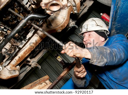 mechanic working on a broken down vehicle - stock photo