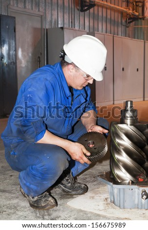 mechanic working on a broken down vehicle, transmission repair - stock photo