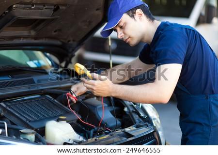 Mechanic working on a car engine - stock photo