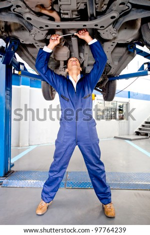 Mechanic working on a cars chassis at the garage - stock photo