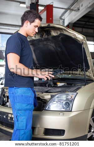 Mechanic working on a digital tablet while standing besides car