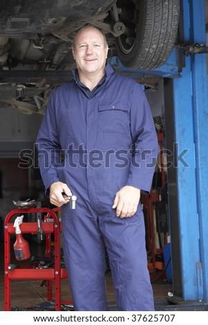 Mechanic working on car - stock photo