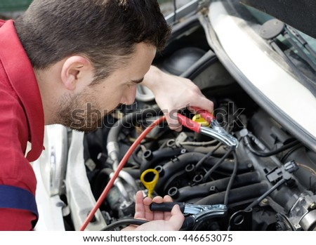 mechanic working on car engine with electricity cables