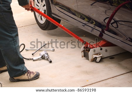 Mechanic working on car using various tools to change tires on a vehicle. - stock photo