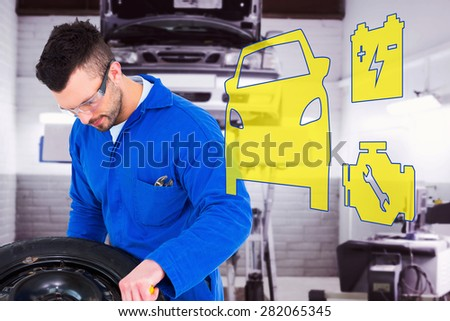 Mechanic working on tire against auto repair shop - stock photo