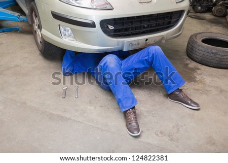 Mechanic working under car in garage - stock photo