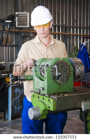 mechanic works at the lathe at factory - stock photo