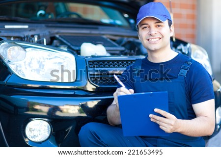 Mechanic writing on a clipboard - stock photo