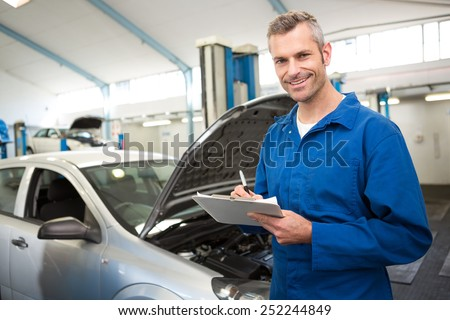 Mechanic writing on a clipboard at the repair garage - stock photo