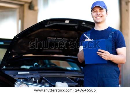 Mechanic writing on clipboard - stock photo