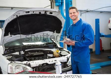 Mechanic writing on clipboard looking at camera at the repair garage - stock photo