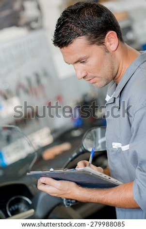 Mechanic writing on his clipboard