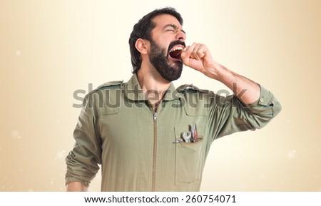 Mechanic yawning over ocher background  - stock photo