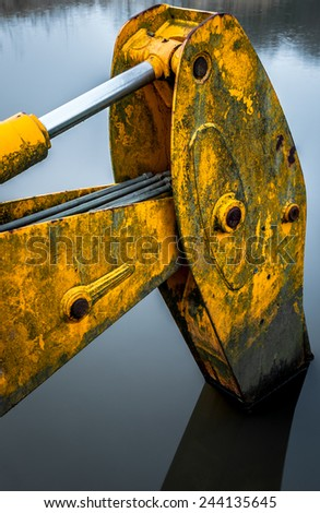 Mechanical dredger partly submerged in water. - stock photo