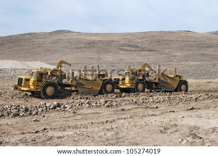 Mechanical earth movers working in tandem mode - stock photo