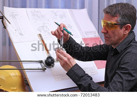 Mechanical engineer analyze his design. Measuring dimensions of metal model with a divider caliper. - stock photo