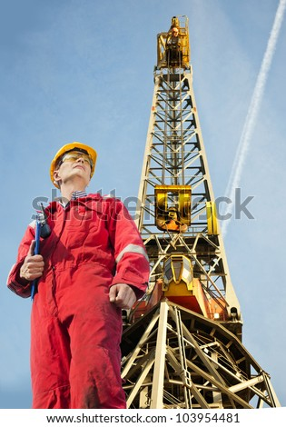 Mechanical Engineer with a clipboard in front a tall harbor crane - stock photo