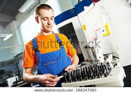 mechanical industrial worker measuring detail near metalwork machining center in tool manufacture workshop. Focus on labor face - stock photo